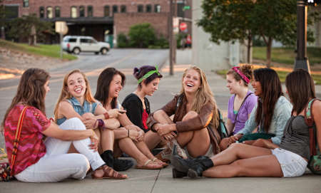 sidewalk talk: Eight pretty young mixed group of teenagers outdoors