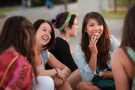 Interested female teenager in conversation with friends