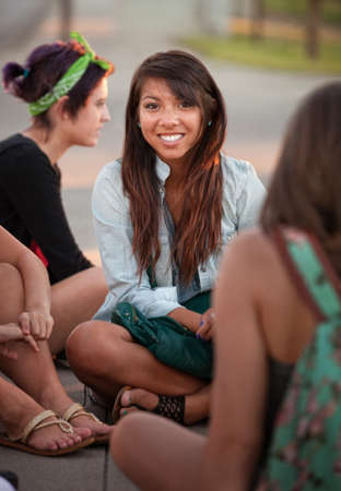 sincere girl: Grinning Filipino girl with friends sitting cross legged  Stock Photo