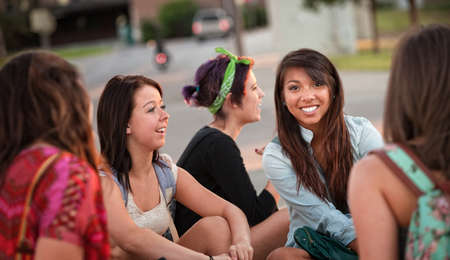 Diverse group of happy teenage girls sitting and talking photo