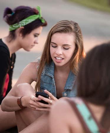 Cute blond teenage girl using her cell phone Standard-Bild