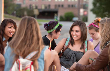 college dorm: Young woman laughing with her friends sitting outside