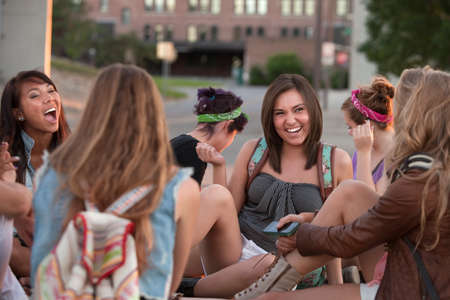 dorm: Group of female students sitting outside laughing together Stock Photo