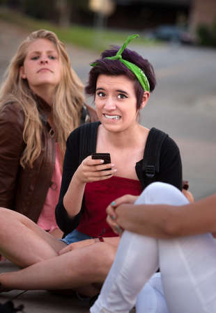 insecure: Embarrassed teenage girl holding phone outside with friends