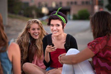 Excited teenage girls looking at a phone outside photo