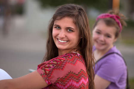 Happy Caucasian teen smiling with friend behind her photo
