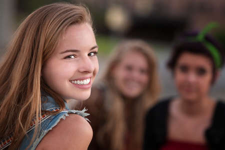 Glimlachend tienermeisje met paar vriendinnen buitenshuis