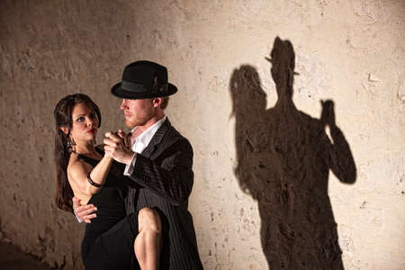 woman  shadow: Attractive tango dancers under spotlight in urban setting