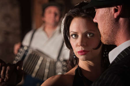Beautiful tango dancer with partner and accordion musician photo