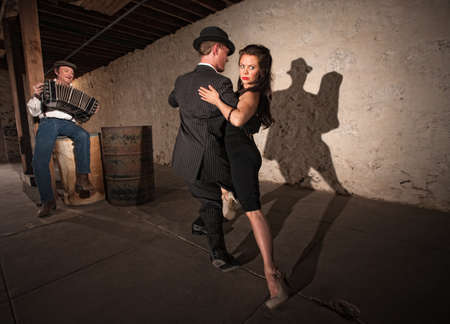 concertina: Bellows musician with Tango dancers in spotlight