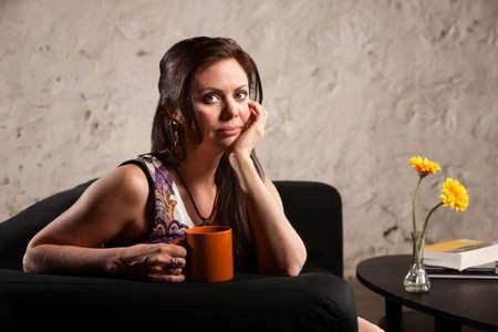 planta de cafe: Serious Caucasian mujer morena taza sentado en el interior y la celebración de