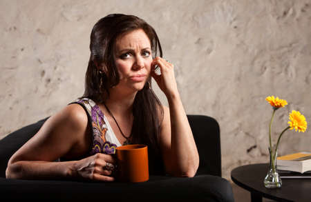 puckering lips: Worried woman holding coffee mug and puckering her lips