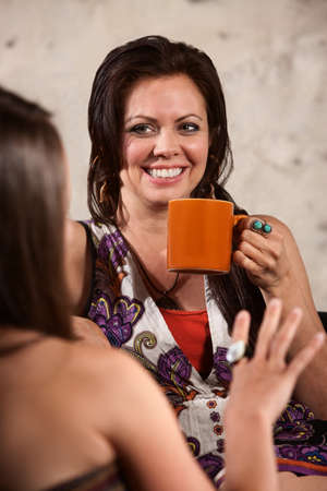 sexy funny: Happy Caucasian brunette drinking coffee and talking with friend Stock Photo