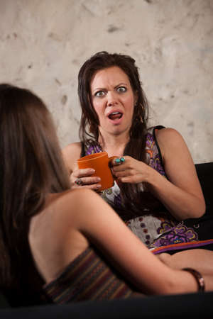 outraged: Shocked woman drinking coffee and sitting with friend Stock Photo