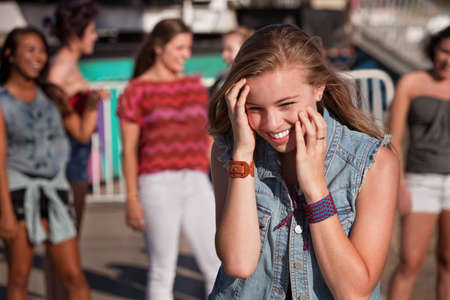 bashful: Shy giggling teenage girl covering her face at carnival Stock Photo