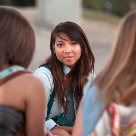 between: Calm young Native American teenager between two friends Stock Photo