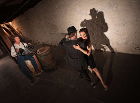 Tango dancers performing indoors with squeezebox player in background