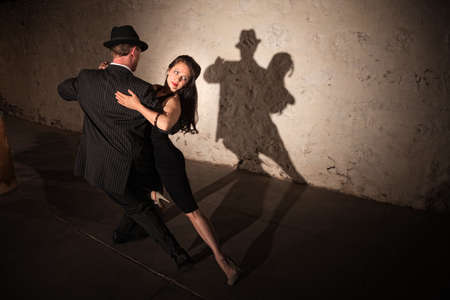 댄스 파트너가 탱고 루틴을 수행하는 아름 다운 여자와 스톡 콘텐츠