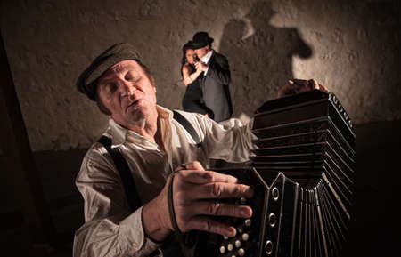 accordion: Singing bandoneon player with two dancers in the background Stock Photo