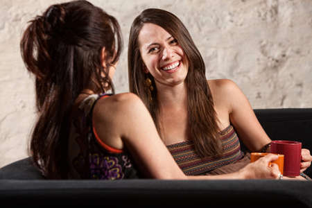 Two beautiful European ladies sitting indoors laughing photo