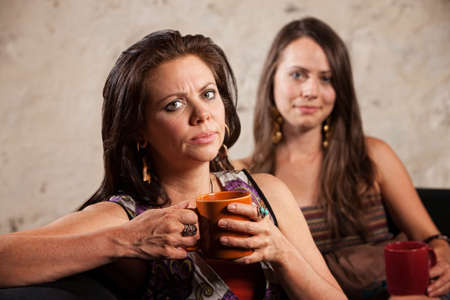 Disappointed Caucasian woman holding mug with friend sitting in background photo