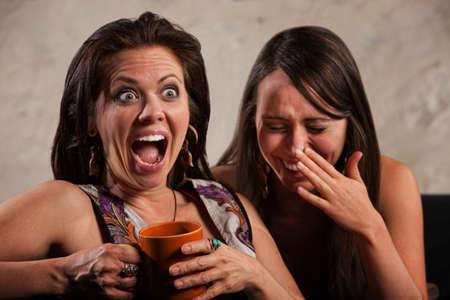 Gritando mujer sosteniendo tazas de café al lado riendo amigo Foto de archivo