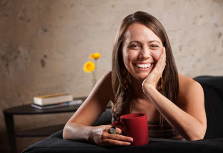 woman on couch: Happy woman with long hair sitting on sofa with mug