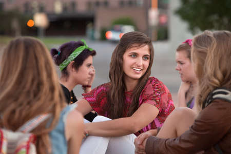 Group of five girls talking and sitting together
