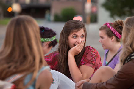 Embarrassed teenage girl with hand on mouth among friends photo
