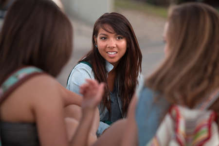 Cute Asian teenage student with friends sitting outside photo