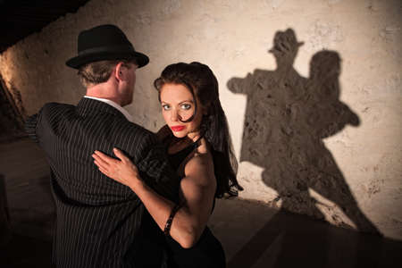 Two tango dancers performing under spotlight indoors photo