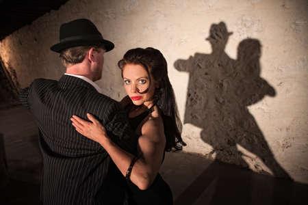 Two tango dancers performing under spotlight indoors