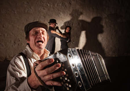 bandoneon: Handsome singer playing accordion with tango dancers in background