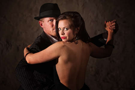 Passionate Caucasian tango partners in 1920s style outfit photo