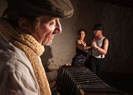 bandoneon: Two European tango dancers turning as squeezebox performer plays