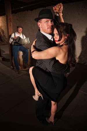 accord�on: Belle femme en noir avec un partenaire de tango danse masculine effectuer Banque d'images