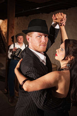 bandoneon: Handsome Tango dancer in pinstripe suit with sexy partner Stock Photo