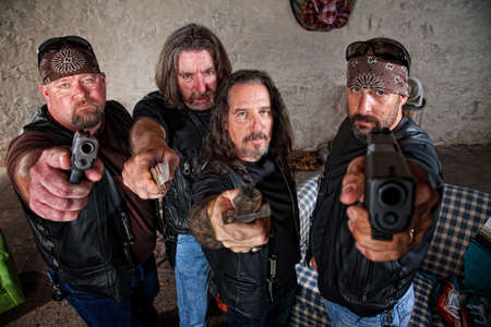 brandishing: Group of four bikers in leather jackets brandishing weapons