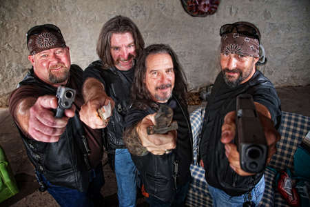 Smiling group of Caucasian bikers in leather jackets with weapons photo