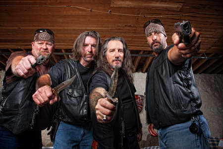 Four tough middle aged white gang members with weapons photo