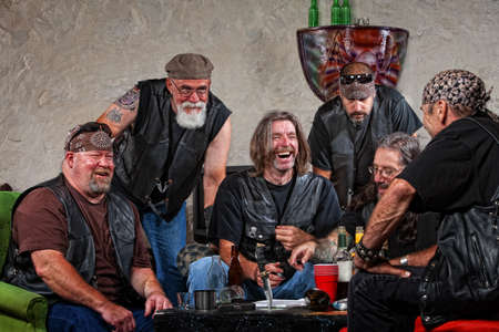redneck: Six male biker gang members laughing with weapons on table Stock Photo