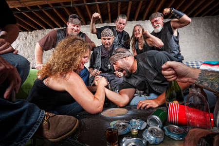 female wrestling: Tough female gang member winning arm wrestling match Stock Photo