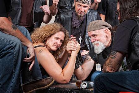 malandros: Mujer seria en el concurso de lucha libre del brazo con banda de motoristas Foto de archivo