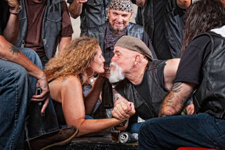 Two biker gang lovers kiss while arm wrestling photo