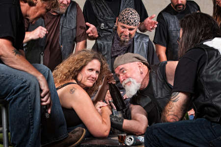 Smiling woman beats gang member in arm wrestling Stock Photo - 15984496