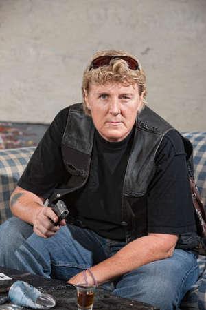 Tough woman in leather jacket points a gun photo