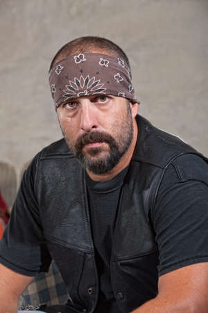 Serious bearded man with bandana and leather vest