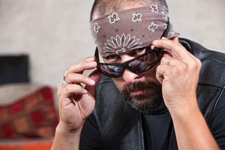 Intimidating male biker in bandana looking over his sunglasses photo