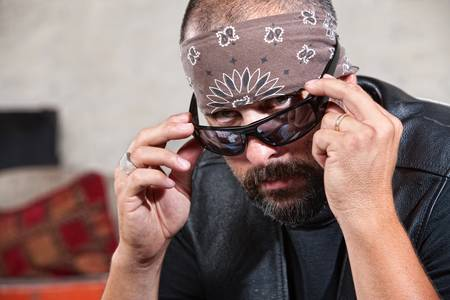 shaved head: Intimidating male biker in bandana looking over his sunglasses