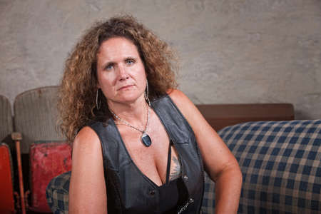 Serious mature biker woman in leather vest sitting indoors
